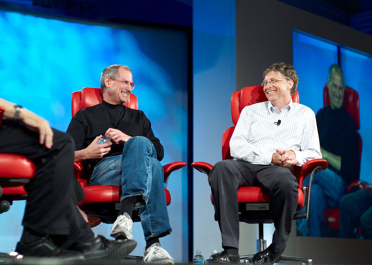 Steve Jobs and Bill Gates on stage, laughing